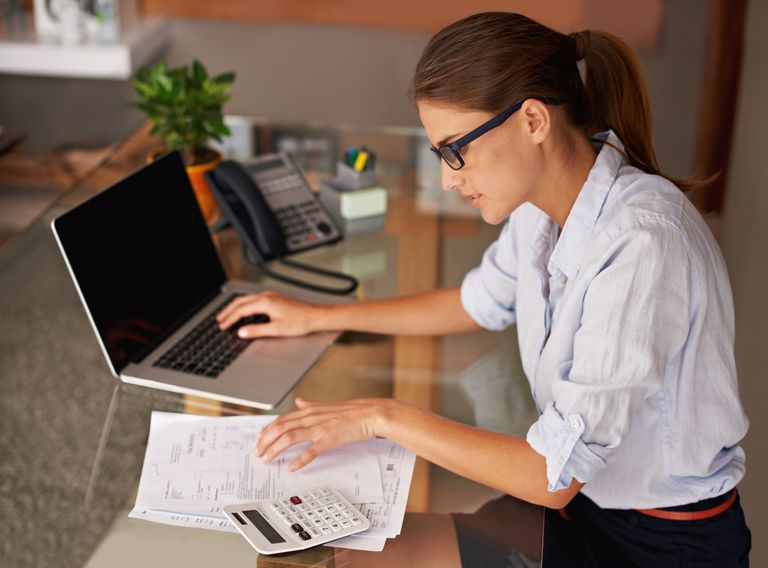 woman with calculator and computer at a desk