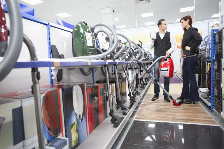 Shop assistant demonstrating vacuum cleaner in electronics store