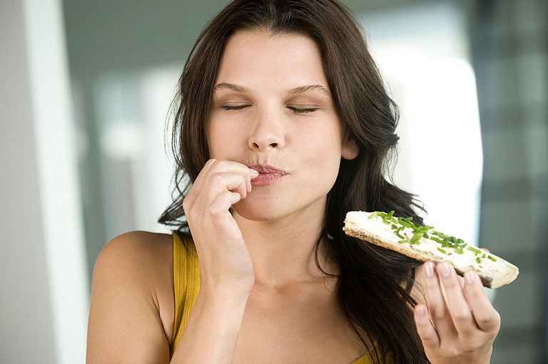 Girl eating with eyes closed