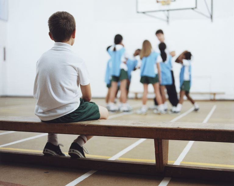 Kids in gym class - one boy sitting on bench