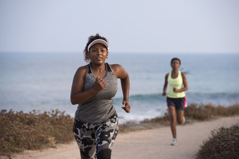 Two African American women running along a trail by the ocean