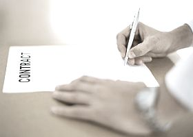 hand with pen signing book contract