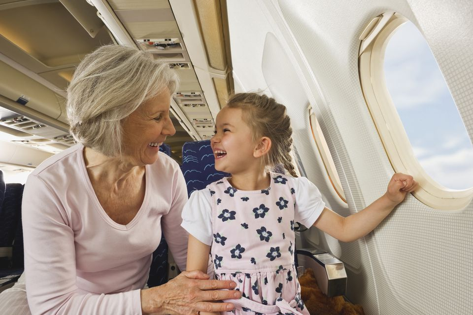 Germany, Munich, Bavaria, Senior woman and girl smiling beside window in economy class airliner