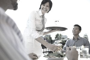Cheerful waitress serving food to businessman at outdoor cafe