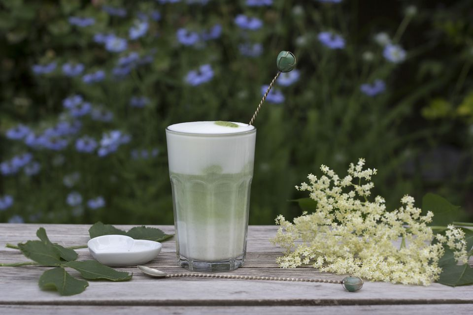 Matcha tea with milk in glass on wood, elder flowers and heart shaped porcellain with spoon