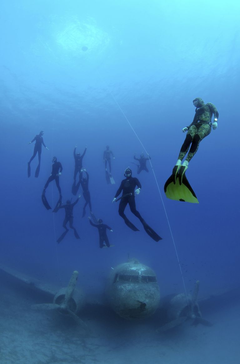 Freedivers underwater with the wreck of the Douglas Dakota airplane in Turkey.