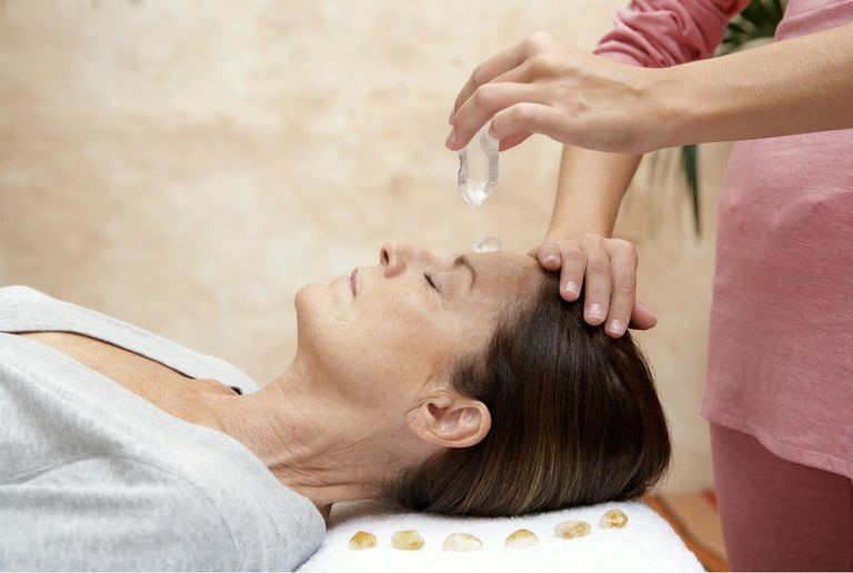 Mature woman receiving crystal healing treatment