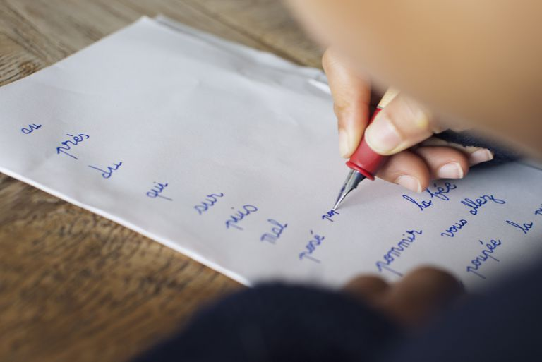 Child writing in cursive on paper, cropped