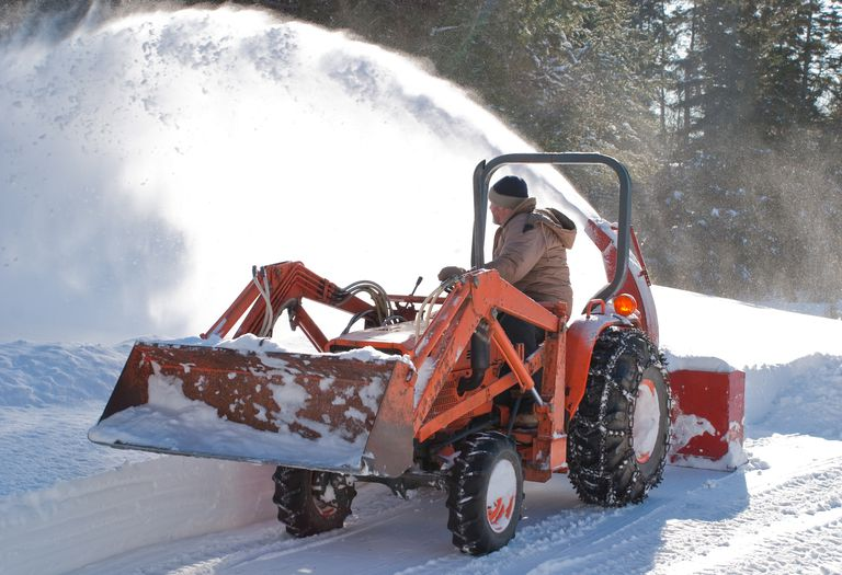 Man on a tractor equipped with a snow blower