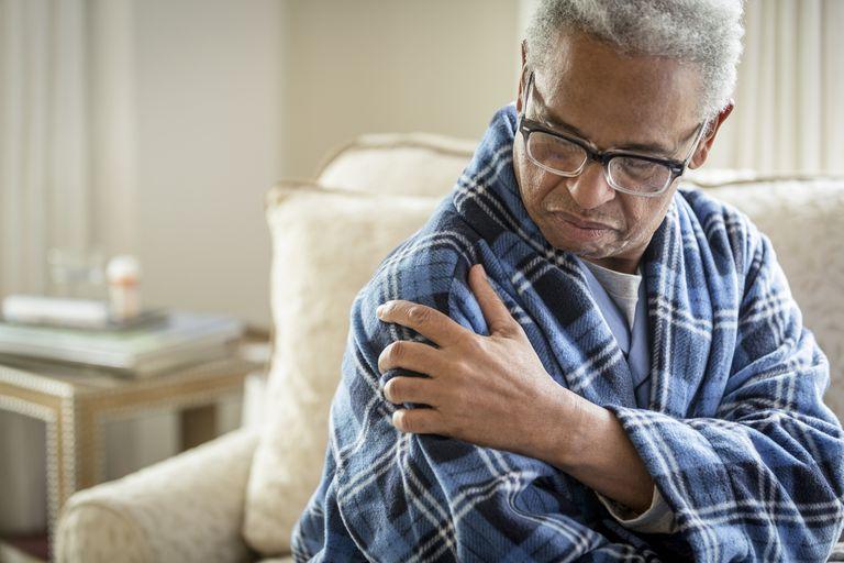 Senior African American man rubbing his shoulder