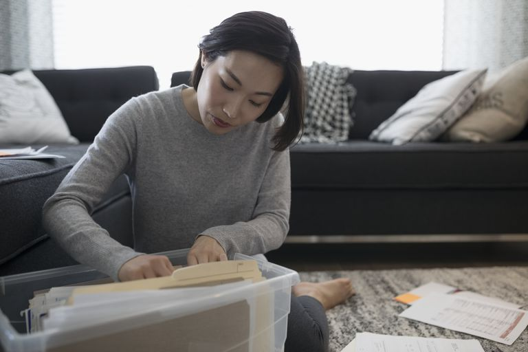 Woman filing financial paperwork on living room floor