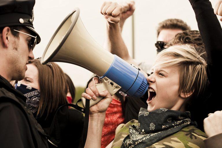 Female protestor shouts at cop through a bullhorn