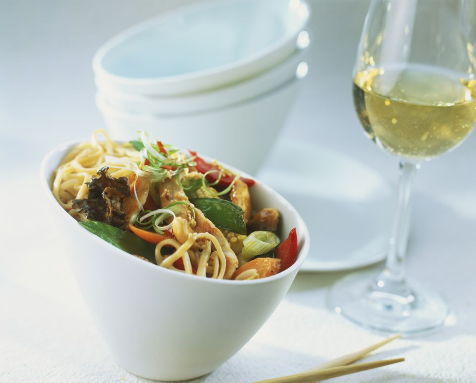 A bowl of chinese food and a glass of white wine.