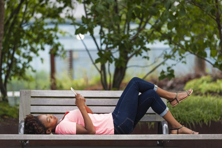 Woman lying on bench wearing jeans