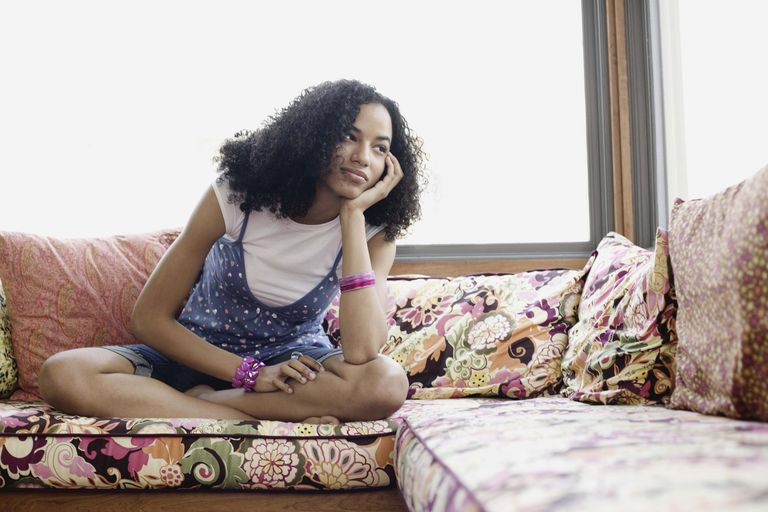 Teenage girl sitting on window seat with head in hand