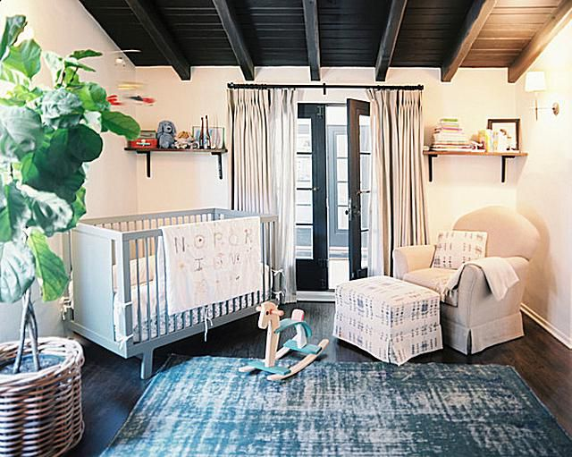 A simple white nursery with rich wood floors and ceiling
