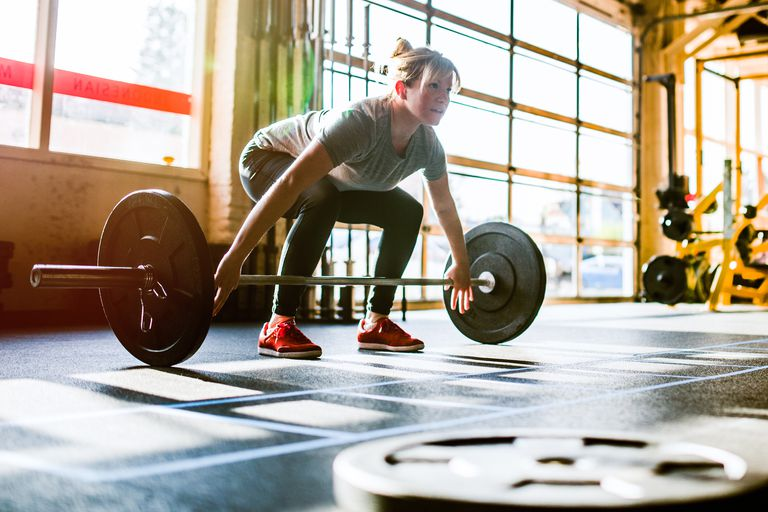 Cross Training Woman Performing Deadlift A young woman exhibits her strength, power, and ability with a heavy dead lift, bright morning sunlight streaming through the window behind her. Horizontal with copy space.