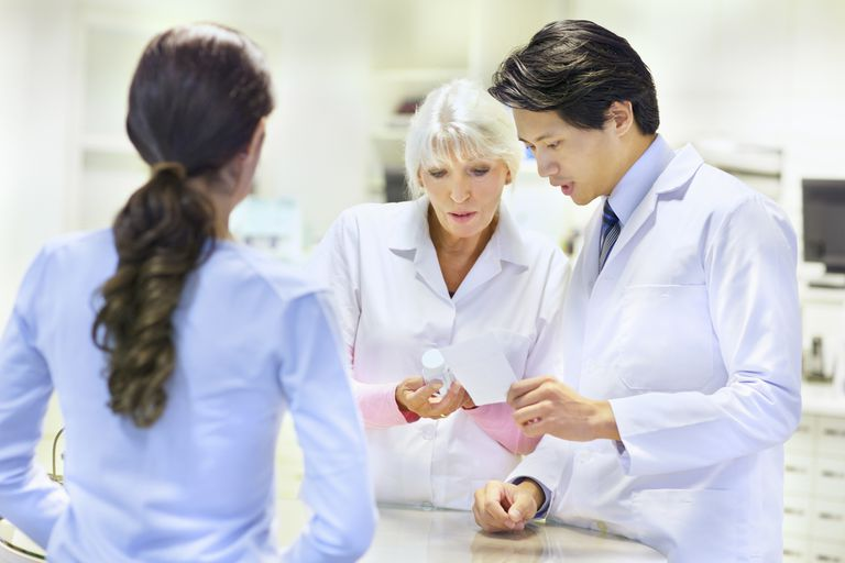 two pharmacists look at pill bottle and prescription in front of patient