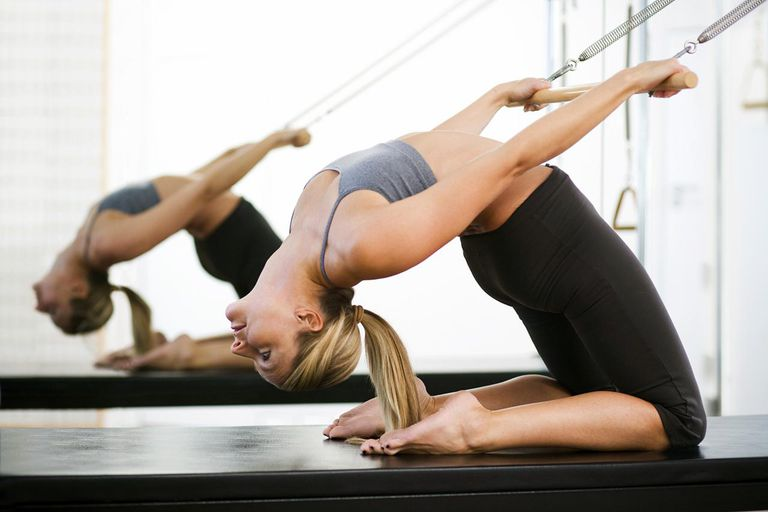 Woman stretching backwards using pilates equipment