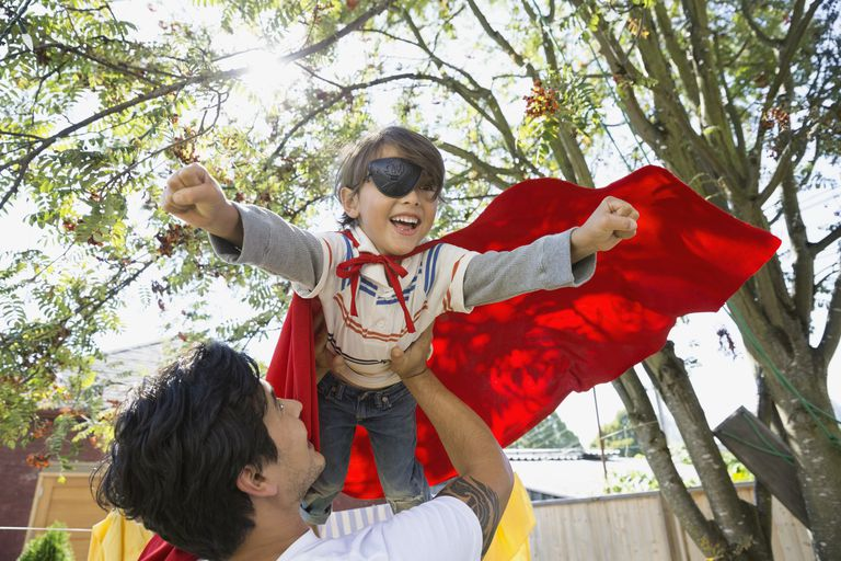 Father flying son in superhero cape overhead