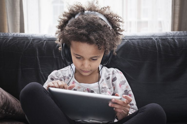 young girl with headphones and tablet