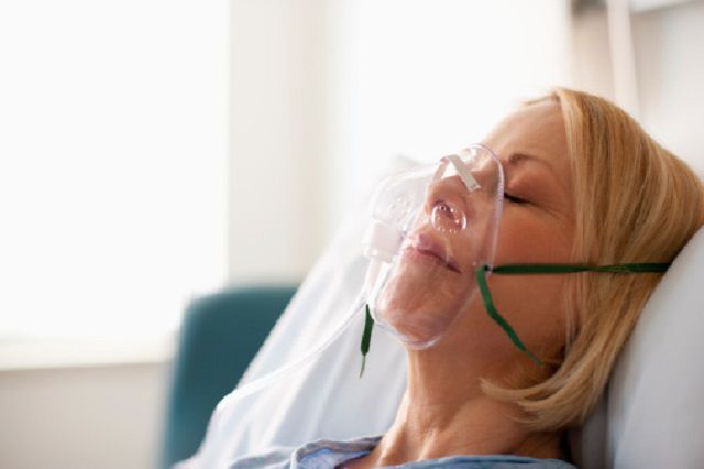 Patient laying in hospital bed in oxygen mask