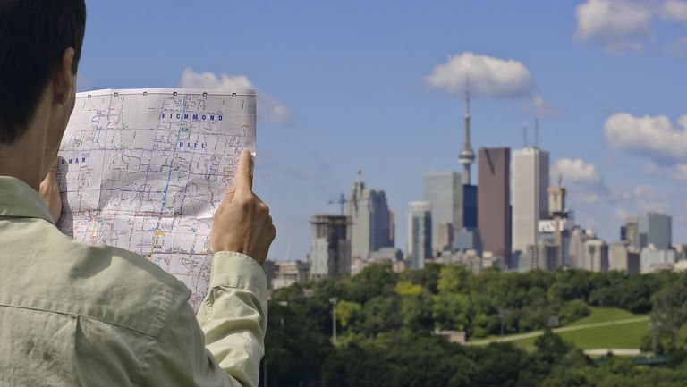 Man holding map with skyline in background, Toronto, Ontario