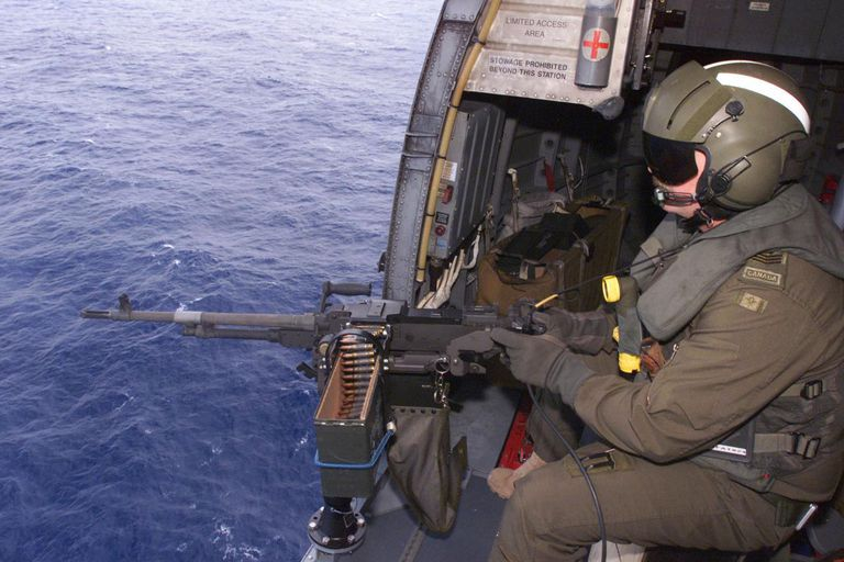 During a training flight, an airborne electronic sensor operator prepares to fire the C-6 machine-gun mounted in the cargo door of one of HMCS Preserver's Sea King helicopters.