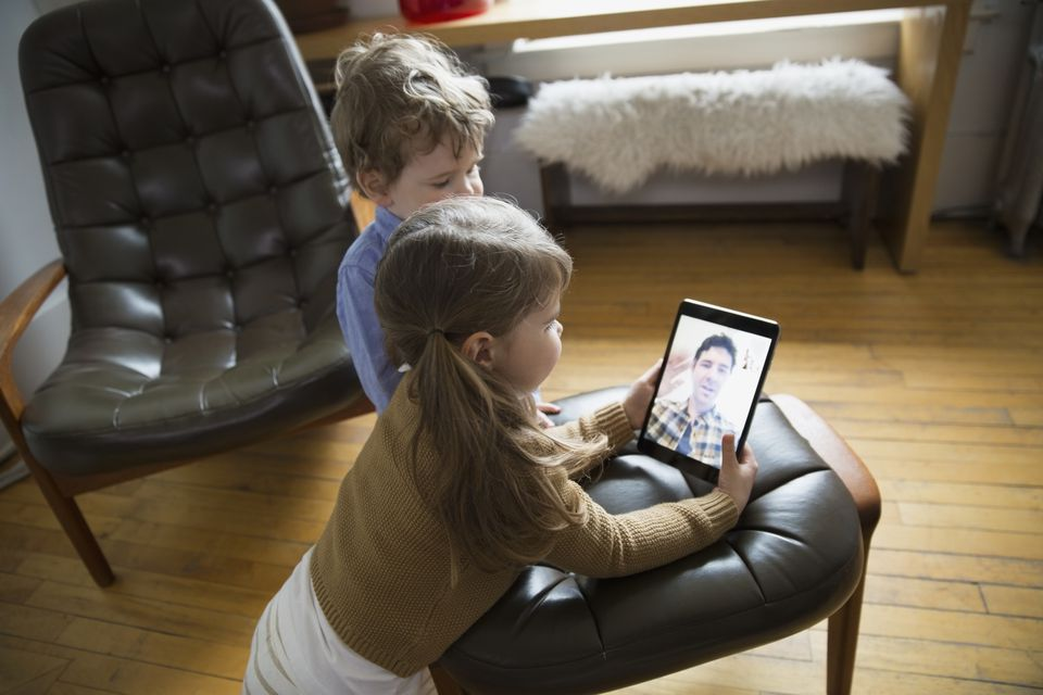 Children talking to father on a tablet