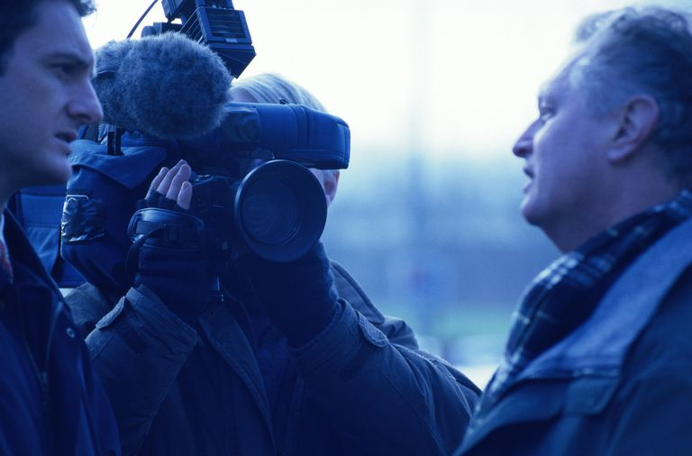 Television crew interviewing mature man, outdoors