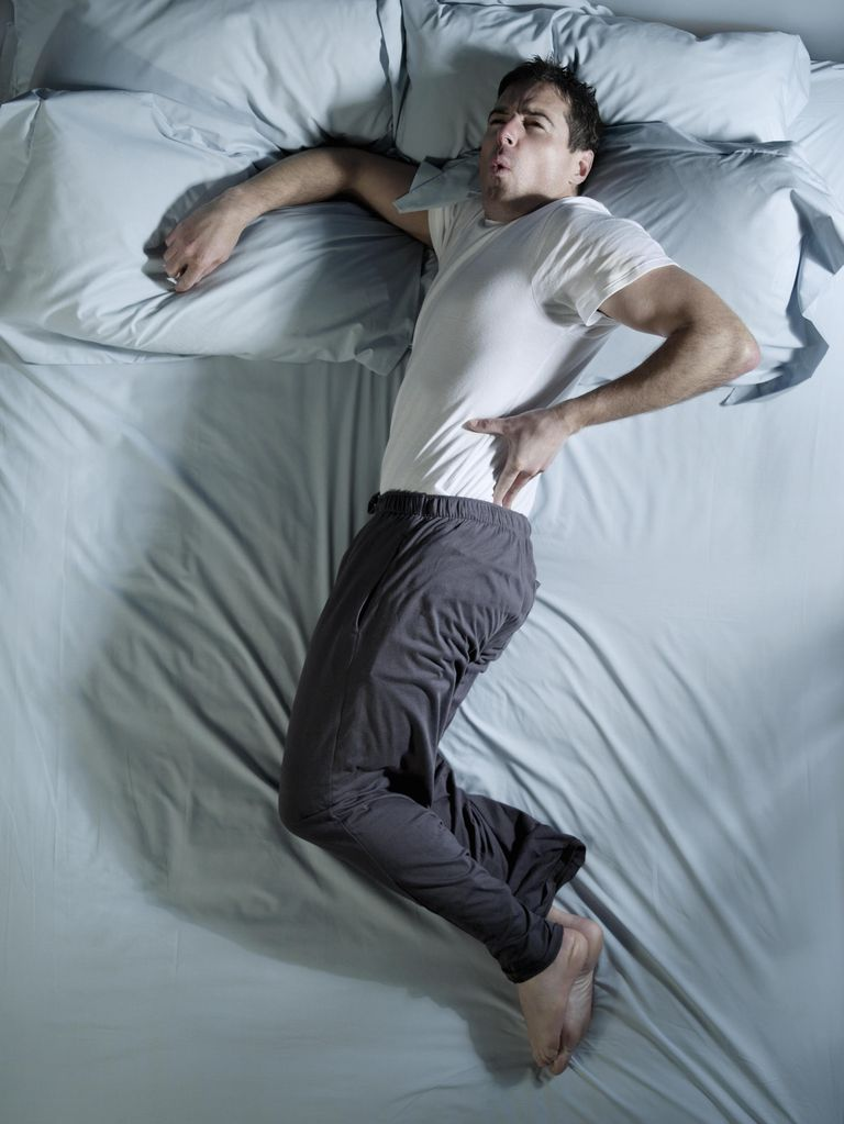 Man lying on bed with back pain