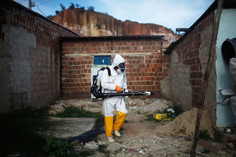 man in hazmat suit spraying for mosquitos transmitting the Zika virus