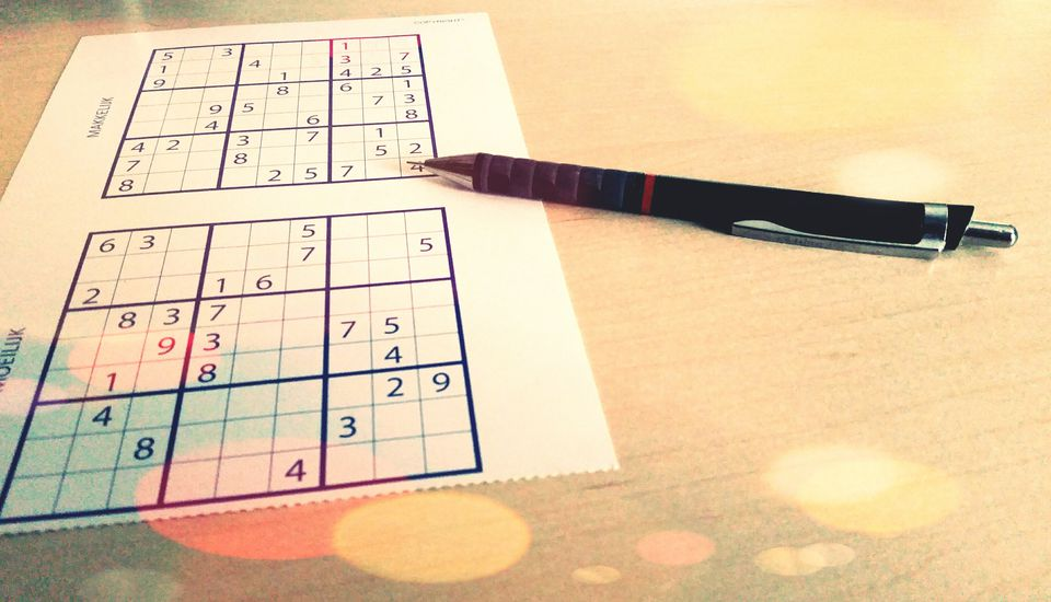 Close-Up Of Pen And Sudoku On Table