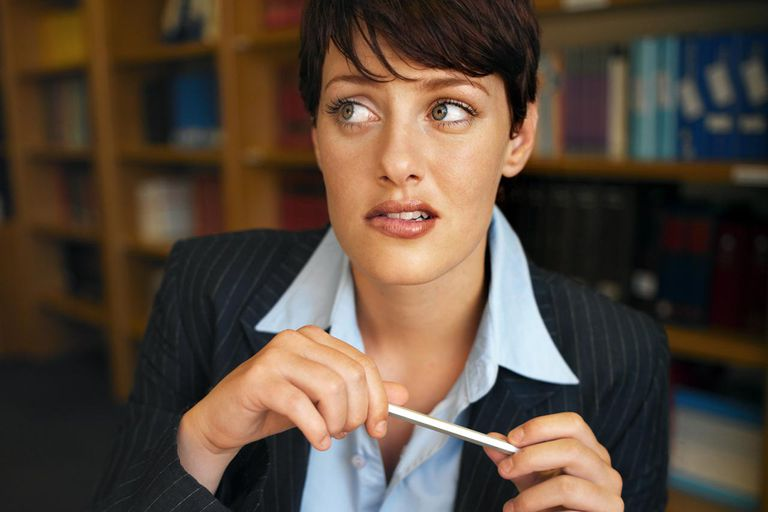 close up front view of businesswoman sitting at desk anxiously completing an aptitude test