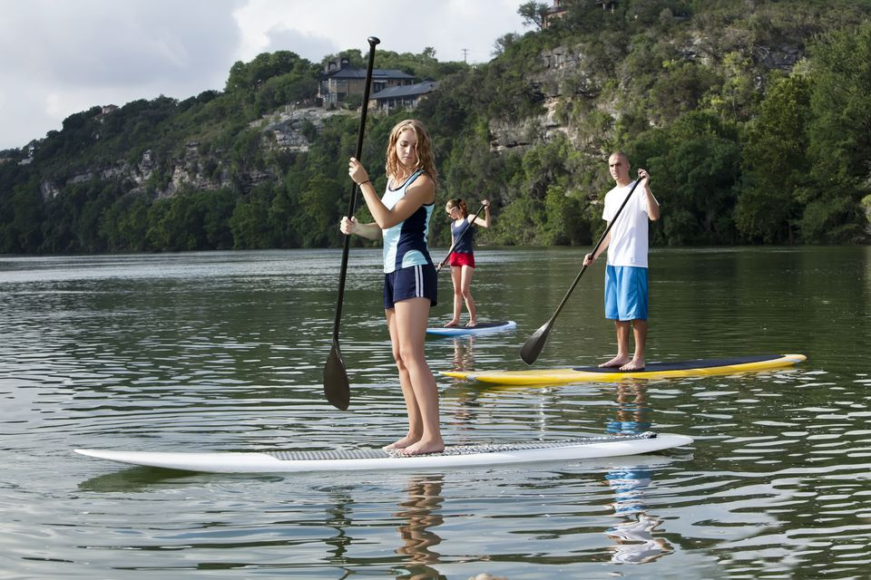 Young adults paddleboarding stand up paddling