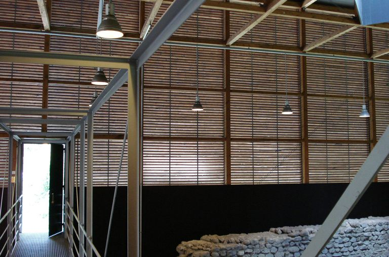 inside a structure of horizontal wooden slats, hanging lights from beams over ancient stone wall