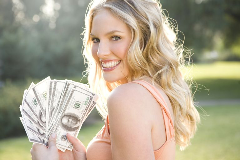 Young woman holding fan of one hundred dollar bills, smiling, portrait