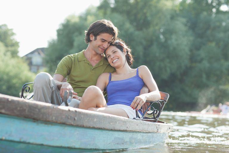 Smiling couple in rowboat on lake