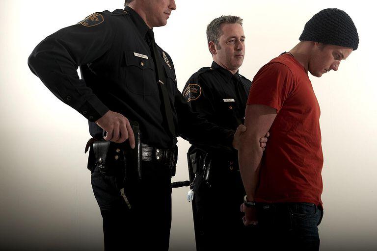 Varón esposado por dos policías