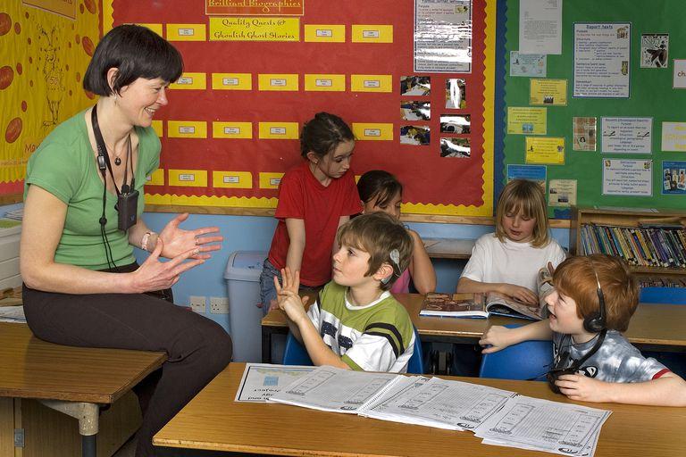 Deaf School boys sign to the teacher each other in School class room