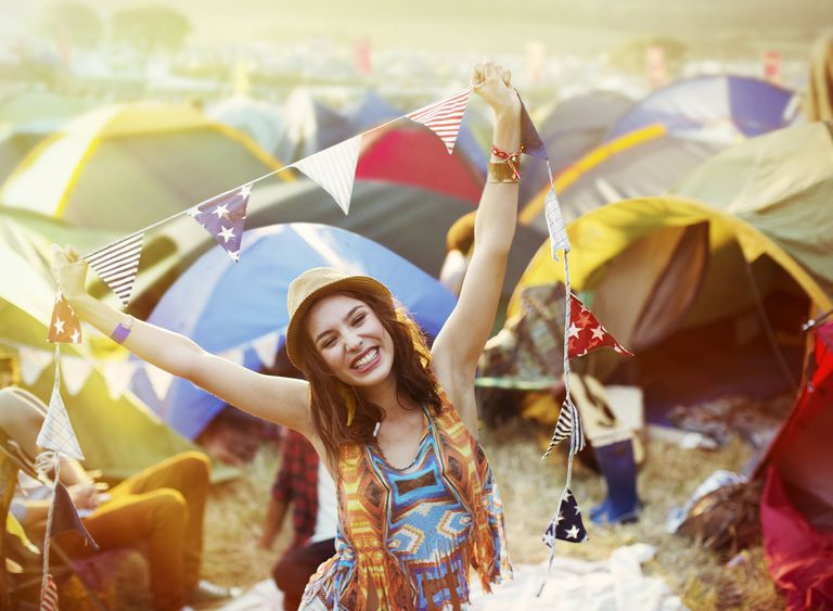 Portrait of enthusiastic woman outside tents at music festival