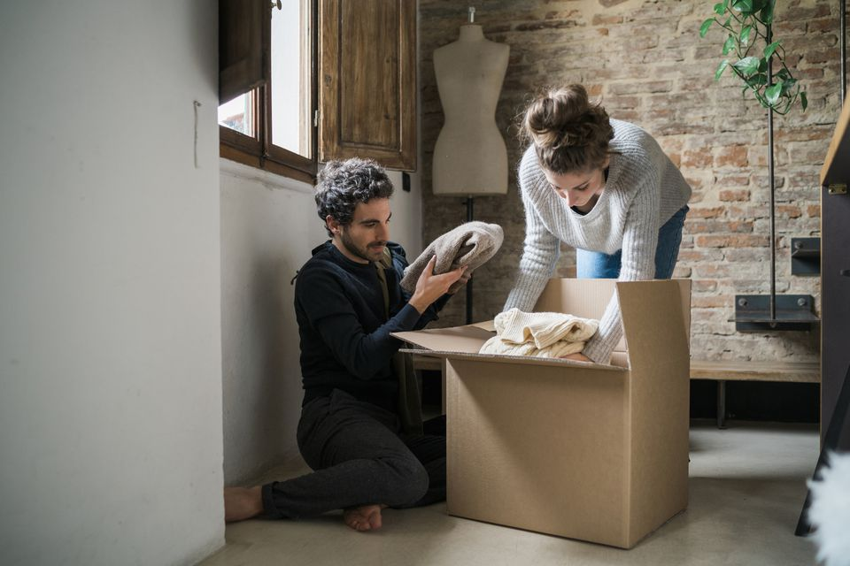 Young couple packing cardboard box on floor