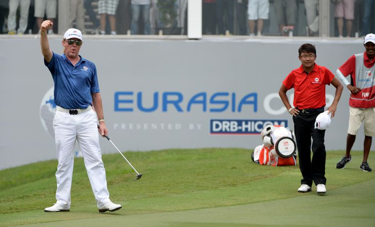 Miguel Angel Jimenez of Team Europe celebrates after holing his putt on the 18th green against Nicholas Fung of Team Asia during singles match play at the 2014 EurAsia Cup