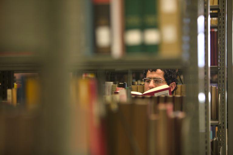 Hombre leyendo un libro detrás de estanterías de la biblioteca