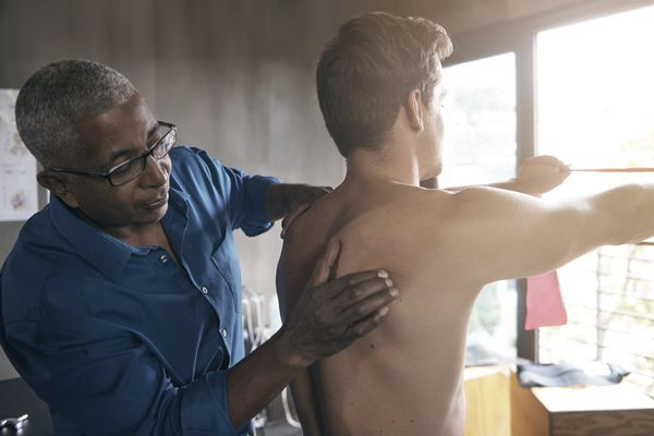 Physical therapist examining man's back