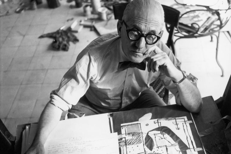Swiss-born architect Le Corbusier, wearing eyeglasses, a bow tie, and shirt sleeves, looking up from a drawing table and an open portfolio