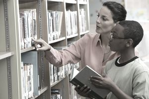 Librarian helping student find books