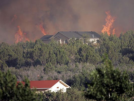 a picture of a wildfire surrounding a home