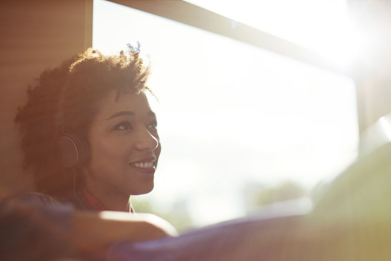 Woman sitting near window in train listening to music
