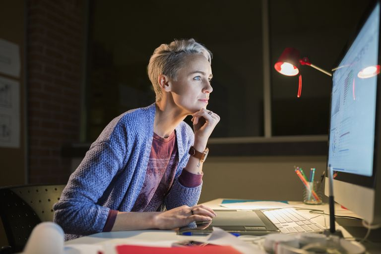 Graphic designer working late at computer in office